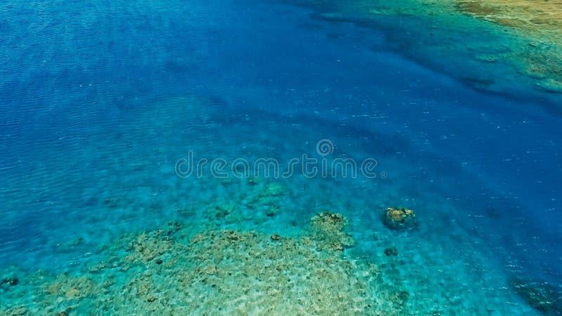 一种巨大珊瑚礁海洋渠道的惊人空中寄生虫图象在镇静天气平坦的水和难以置信的五颜六色的海海洋床的 库存照片