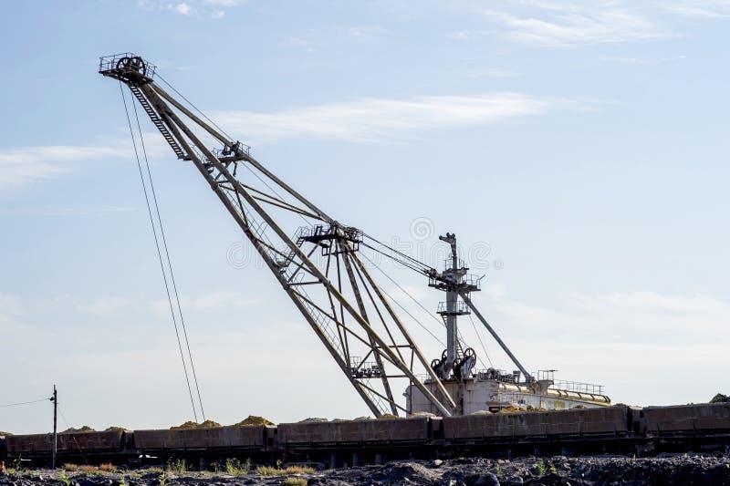 一种巨大的挖掘机在转储超载从从矿的被卸载的火车震动反对一清楚的天空蔚蓝 概念 库存照片