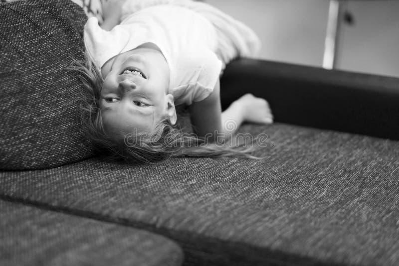 一种快乐的心情的女孩在长沙发 免版税图库摄影
