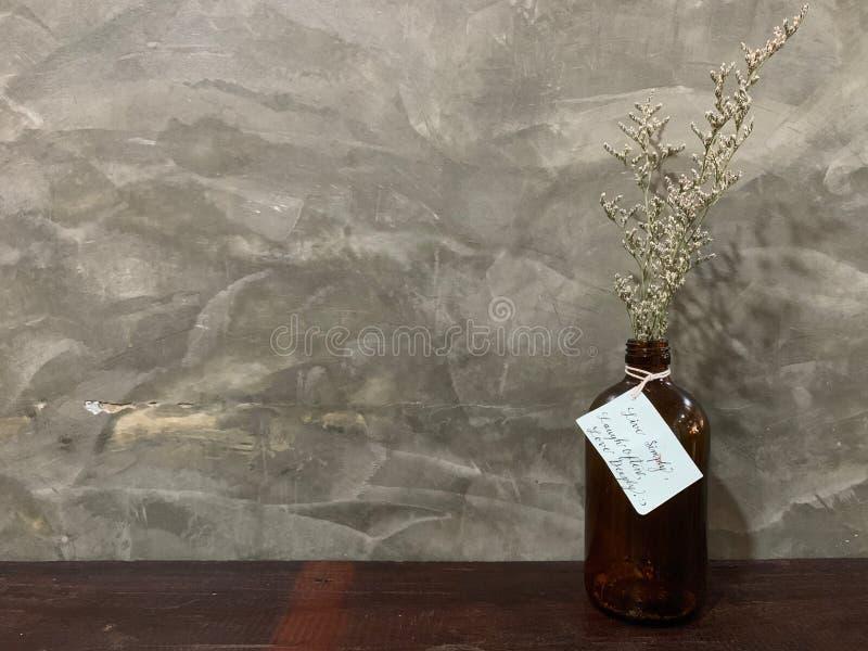 一种白色在一个花瓶的麦小花在木桌上的棕色颜色与水泥墙壁、经典之作和葡萄酒老牌 图库摄影