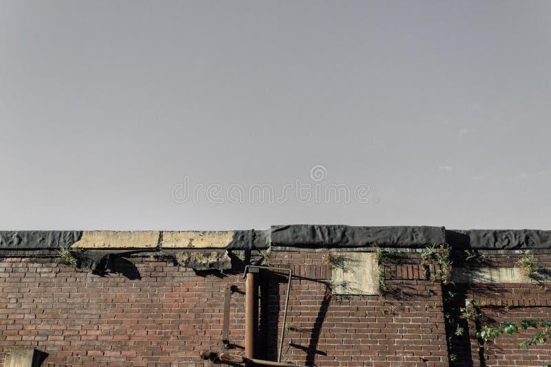 一种老工业仓库、砖、焦油纸和生锈的金属,拷贝空间的屋顶外形 免版税库存图片