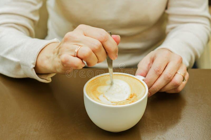 一种鹅掌母搅拌杯 早晨新鲜烹制的卡布奇诺 免版税库存照片