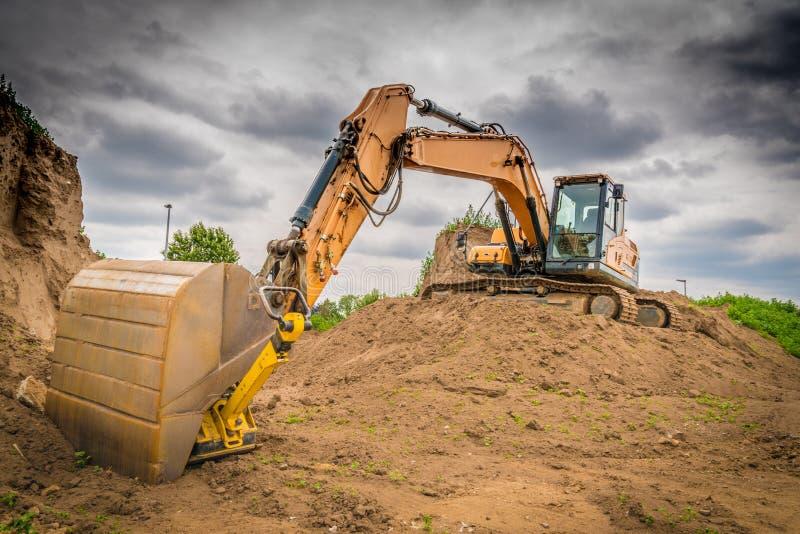 一种黄色挖掘机在工作 库存照片