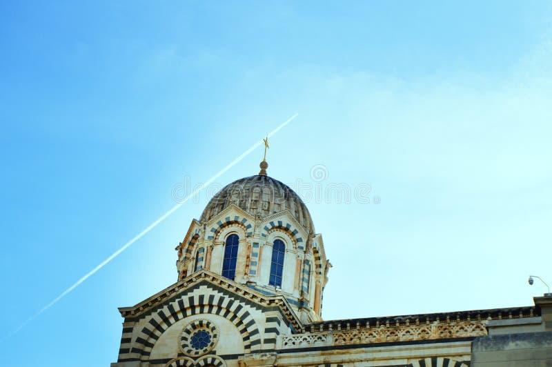 一系列的8张照片-在天空的踪影从在Notre Dame de La加尔德角大教堂的平面飞行在马赛,标志  免版税库存图片
