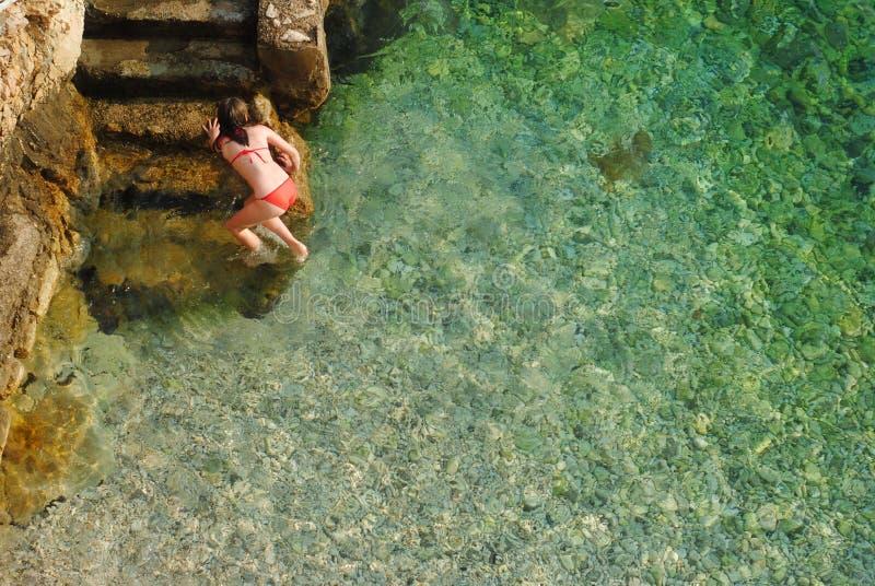 一红色游泳衣离开海和上升的一个女孩在岩石 免版税库存照片