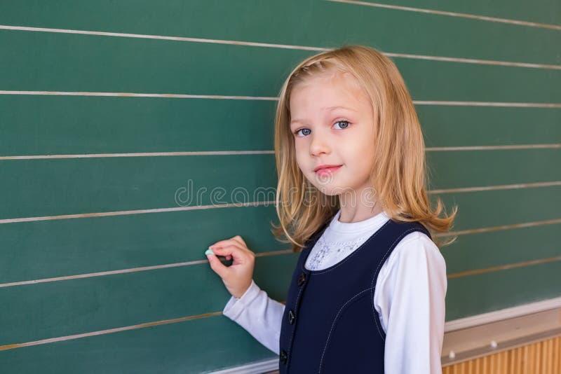 一级学生在绿色黑板的女孩文字在学校教训 免版税图库摄影