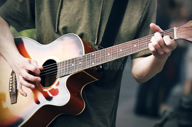 一绿色有冠乌鸦的一个年轻神气活现的人弹一把明亮的色的音响六串吉他 免版税库存图片