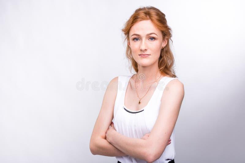 一美丽的在她的面孔的年轻女人与长的红色头发的欧洲,白种人国籍和雀斑的画象 免版税库存图片