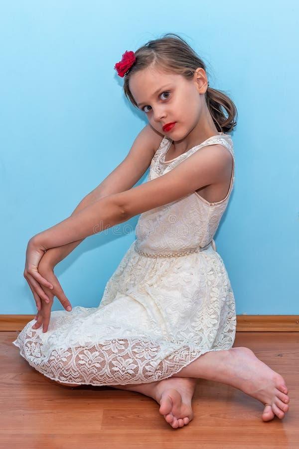 一美丽的女孩摆在坐地板 库存照片