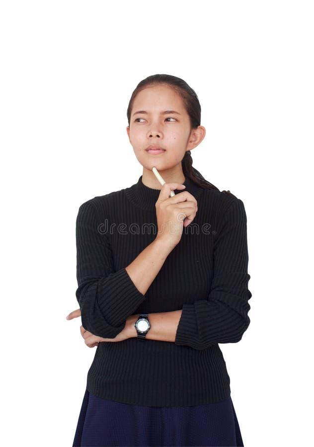 一美丽的女服有拿着一支白色笔的一条蓝色裙子的一件黑女衬衫和严肃认为某事 免版税库存照片