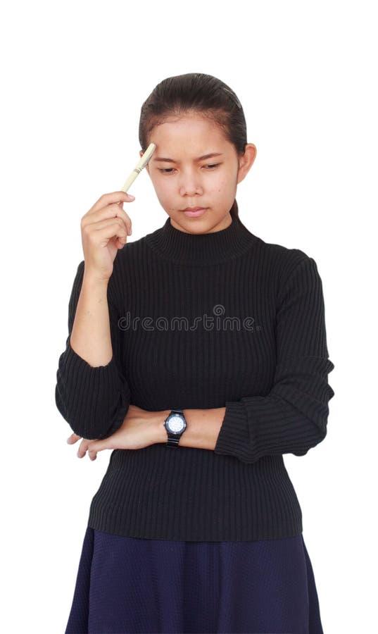 一美丽的女服有拿着一支白色笔的一条蓝色裙子的一件黑女衬衫和严肃认为某事 免版税图库摄影