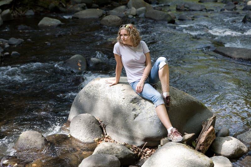 一美丽的年轻女人坐石头在山小河旁边 图库摄影