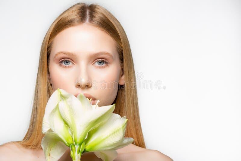 一美丽的年轻女人的半身画象有水芋属花的在干净的背景,健康生活方式,秀丽 库存照片