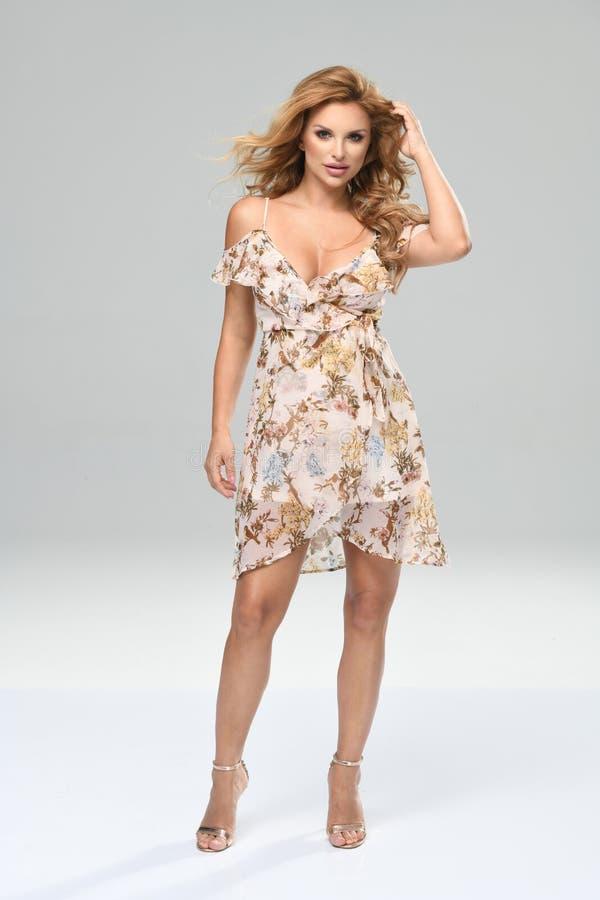 一美丽的年轻女人的时尚照片一件俏丽的礼服的有花的 免版税库存图片