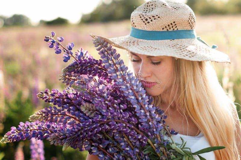 一美丽的年轻女人的画象一个草帽的有被采的羽扇豆花束的  图库摄影