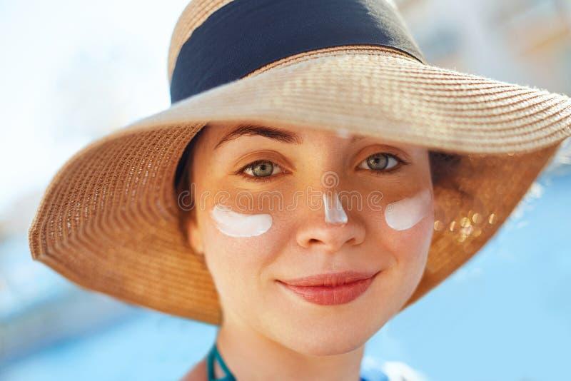 一美丽的年轻女人的画象,微笑,在泳装,与太阳保护奶油的被抹上的面孔 免版税库存照片