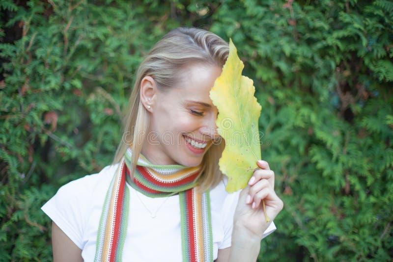 一美丽的年轻女人的豪华画象有自然构成的拿着在被弄脏的绿色背景的一片大绿色叶子 温泉和 库存照片