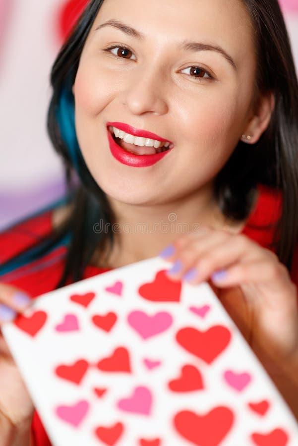 一美丽的年轻女人采取与心脏的一张卡片与爱的声明 日s华伦泰 免版税库存照片