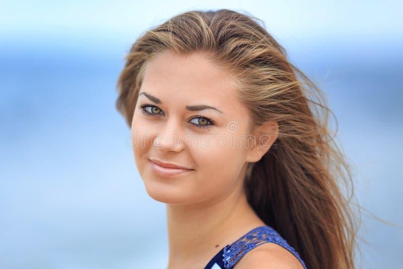 一美丽的愉快的少女的画象海滩的在一件镶边T恤杉,振翼在风的头发 免版税图库摄影