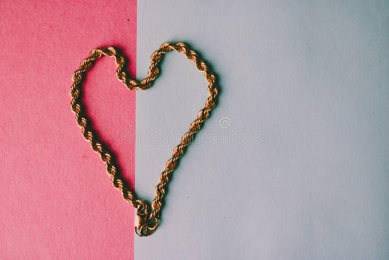 一美丽的金黄欢乐链子独特编织的纹理以在桃红色紫色蓝色背景和拷贝空间的心脏的形式 免版税库存照片