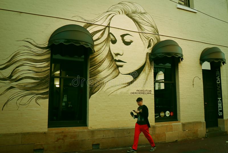 一美女的一张graffitied家的这画象在墙壁上的 库存照片