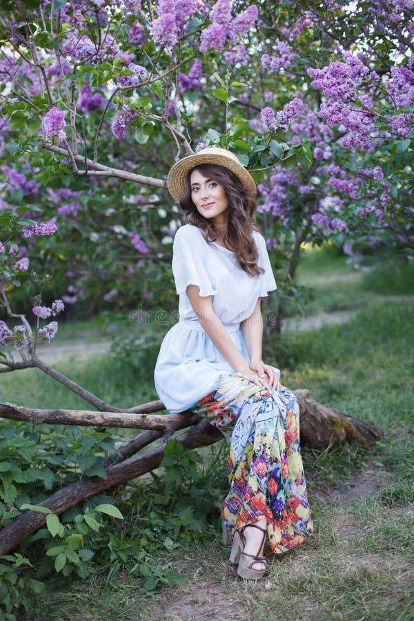 一美女的室外时尚照片有卷发的在有一顿浪漫野餐的一件典雅的葡萄酒礼服在开花的树中 免版税库存图片