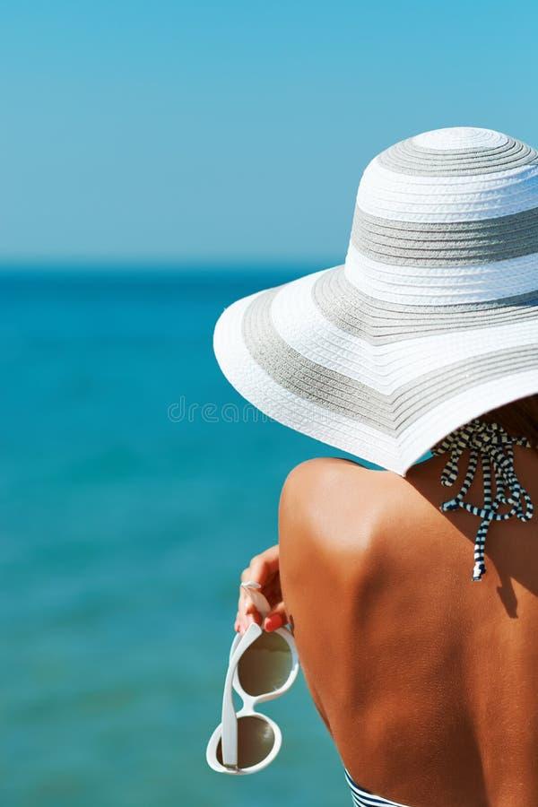 一美女的性感的后面比基尼泳装、创造性的帽子和太阳镜的在海背景 免版税库存图片