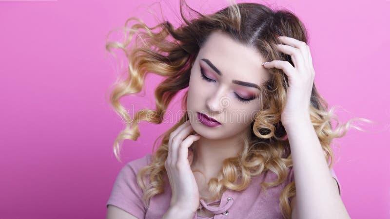 一美女的搬运工桃红色演播室背景与卷曲的头发和构成,秀丽的概念和青年时期的 库存照片