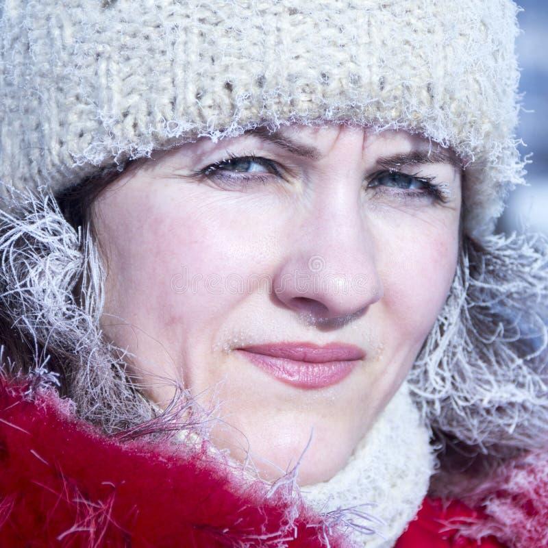一美女的画象一件红色夹克和一个白色被编织的盖帽的在霜树冰的冬天在头发和睫毛 库存照片