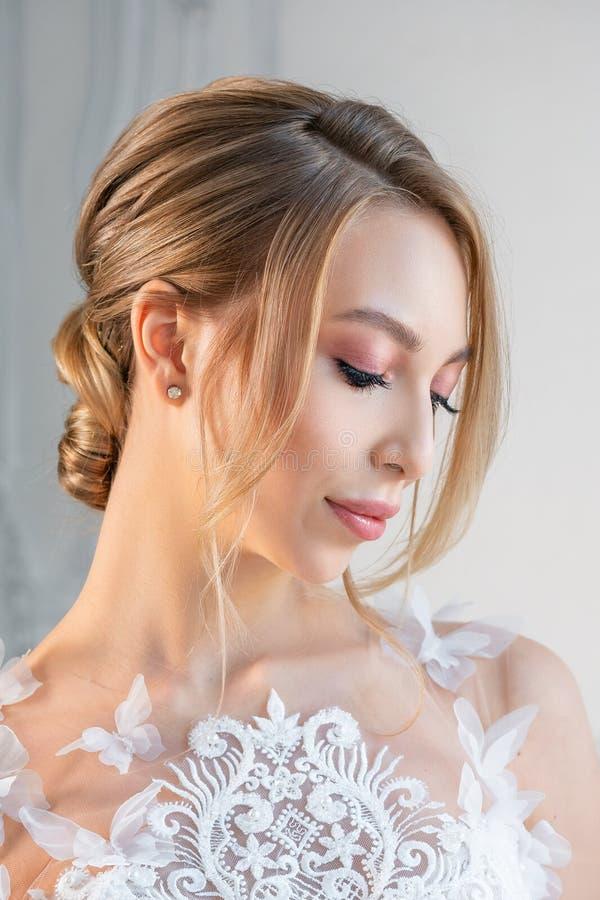 一美女的画象一白色婚纱的有一种美好的构成和发型的 库存图片