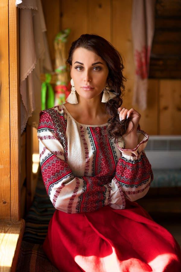 一美女的画象坐由窗口的一件全国礼服的 库存照片