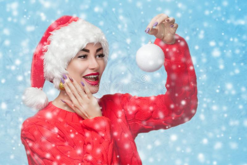 一美女的画象拿着在雪花backg的一件红色圣诞老人项目帽子和被编织的红色毛线衣的一个白色圣诞节快乐球 库存照片