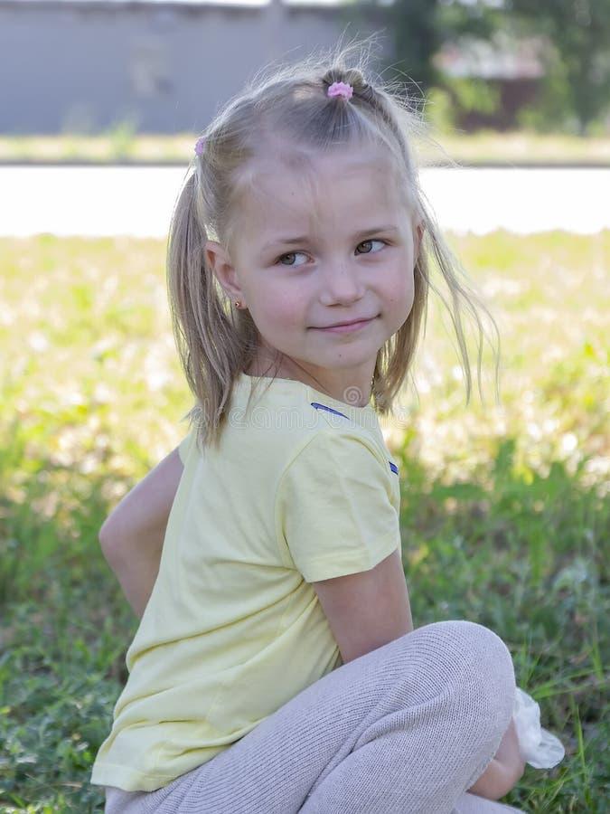一美女的画象草坪的背景的 库存照片