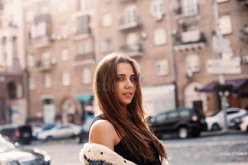 一美好女孩摆在的迷人的画象室外 牛仔布夹克、红色头发、太阳镜和光秃的肩膀 时髦时尚样式 库存图片