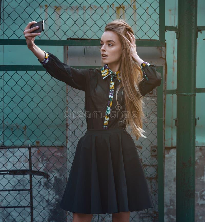 一美好的少妇selfie的画象在有做V形标志的智能手机的公园 免版税库存照片