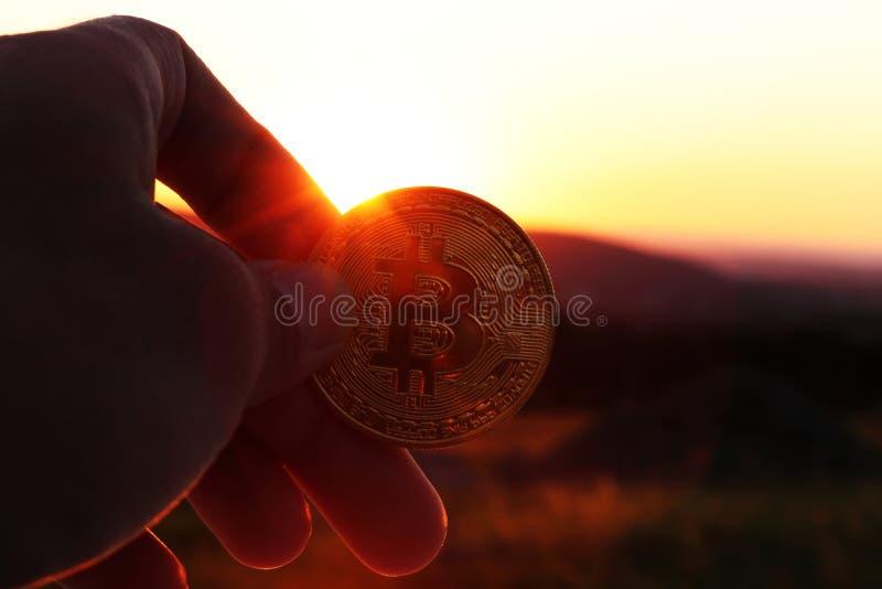 一美好的金黄bitcoin在手中某些投资顾问或银行家有日落和山的 库存照片