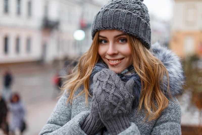 一美妙的年轻女人的画象有美丽的蓝眼睛的与在甜微笑的自然构成在一个被编织的帽子 免版税库存图片