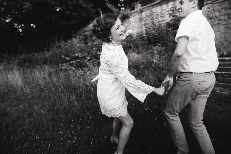 一美妙的爱情故事 走在城堡附近老墙壁的年轻夫妇  E 免版税库存照片