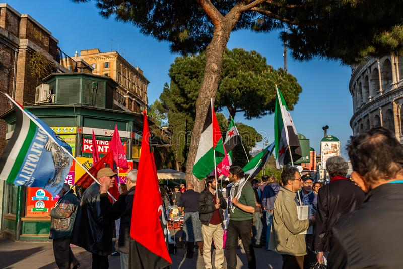 一群人有旗子的以前聚集了在抗议集会上靠近罗马斗兽场在罗马 库存图片