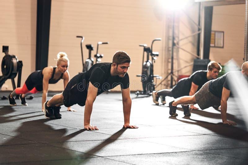 一群在健身房做俯卧撑的健身男 库存图片