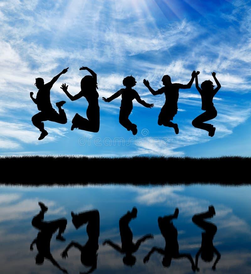 一群愉快的人的剪影跳跃 库存照片