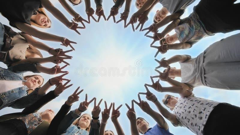 一群朋友用他们的手指做一个圆圈 团结的概念 库存图片