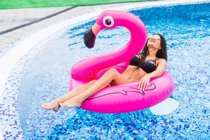 一群桃红色火鸟的女孩在太阳镜的水池 夏天职业 免版税库存图片
