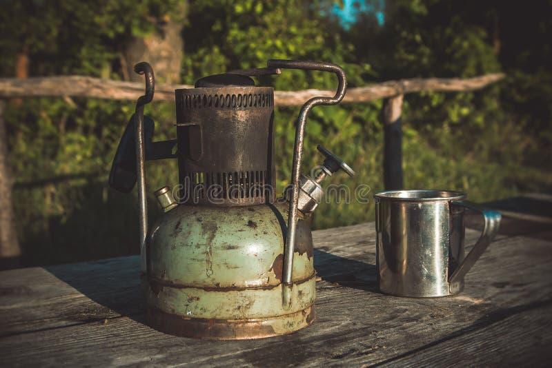一老苏联煤油primus和钢杯子在自然 免版税库存图片