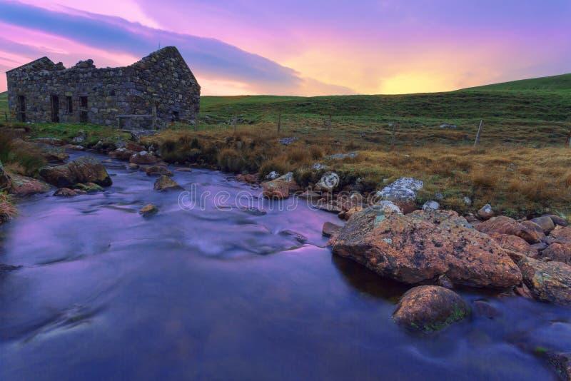 一老被破坏的bothy在苏格兰人停泊,并且小河流经 免版税库存照片