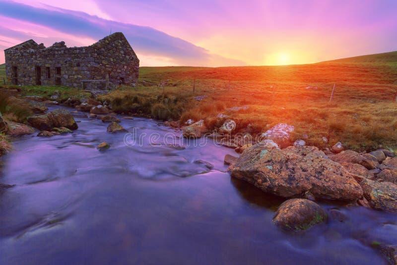 一老被破坏的bothy在苏格兰人停泊,并且小河流经 图库摄影