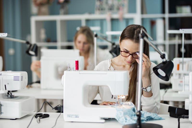 一聪明俏丽的深色的妇女佩带的白色衬衫缝合与电缝合机器 时尚,裁缝的 免版税库存照片