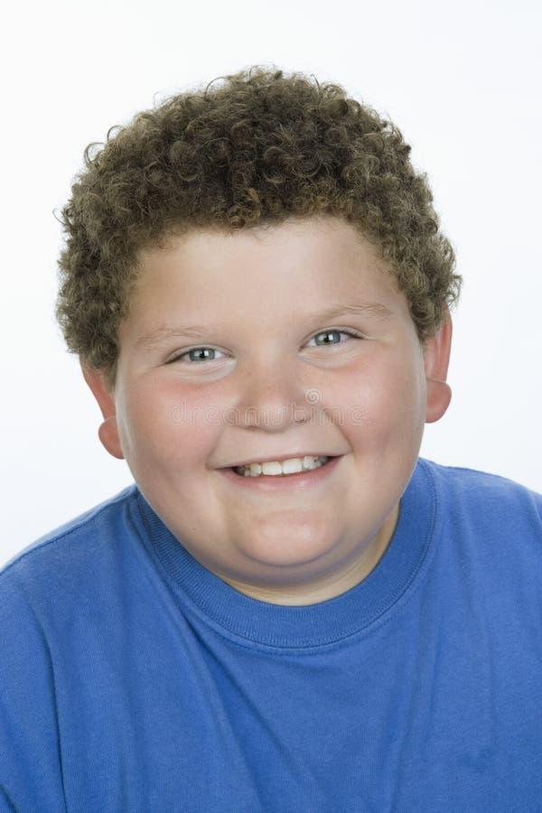 一肥胖十几岁的男孩微笑 库存图片