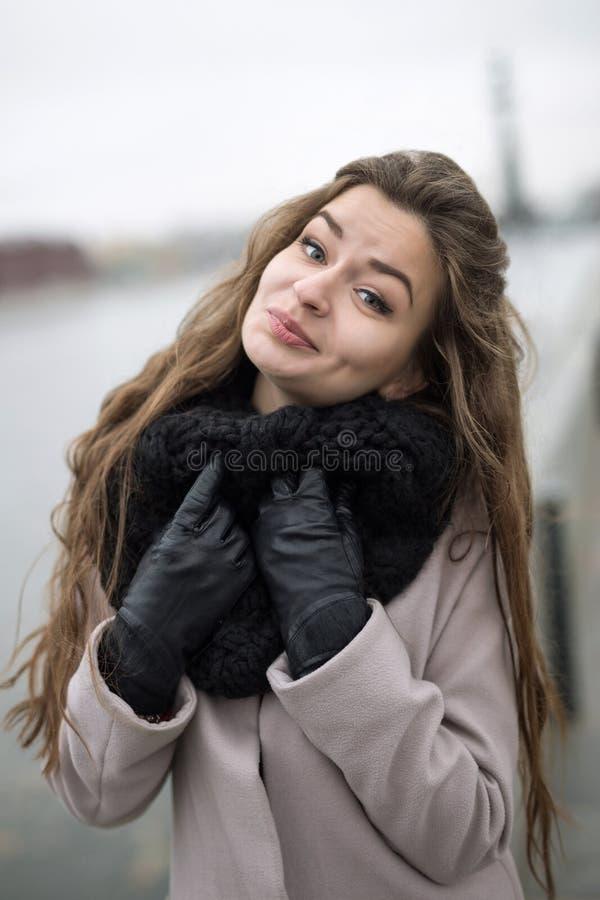 一自然构成逗人喜爱微笑的美丽的女孩对照相机 一件黑外套、一条围巾和一件红色礼服的女孩反对灰色天空 图库摄影