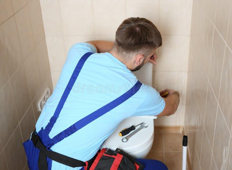 一致的修理的洗手间坦克的专业水管工 库存图片